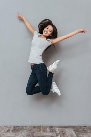 Verticaal beeld van vrij gelukkige vrouw die in studio springt en camera over grijze achtergrond bekijkt