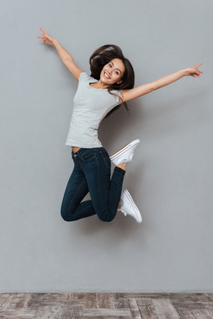 Vertical image of pretty happy woman jumping in studio and looking at camera over gray background