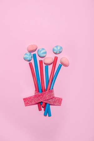 Bouquet of flowers made up with colorful sweet sugar candies over blue