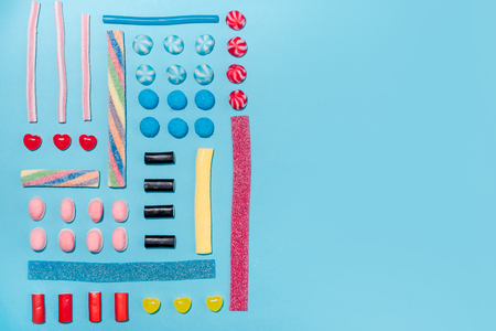 Top view of a colorful sweet sugar candies in a row with copyspace over blue background