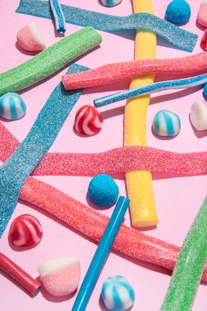 Close up of mixed colorful candies jellies isolated on pink background Stock Photo
