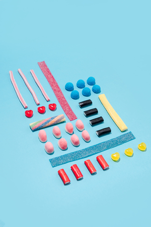 Top view of a colorful sweet sugar candies in a row over blue background