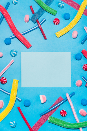 Top view of colorful sugar candies and lollies with envelope in the middle isolated on blue background