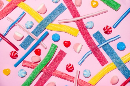 Mixed colorful candies jellies isolated on pink background Stock Photo