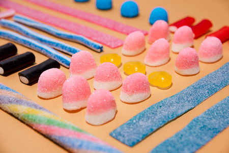 Close up of mixed multicolored sweet candies and lollies isolated on pink background Stock Photo