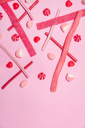 Mix of pink and red sugar jelly candies and lollies isolated on pink background Stock Photo