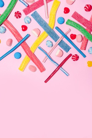 Top view of mixed colorful candies and lollies isolated on pink background