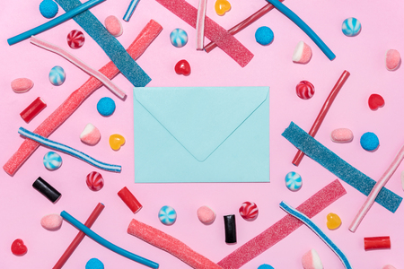 Sweet jelly licorice candy sticks and lollies with blank paper envelope isolated on blue background