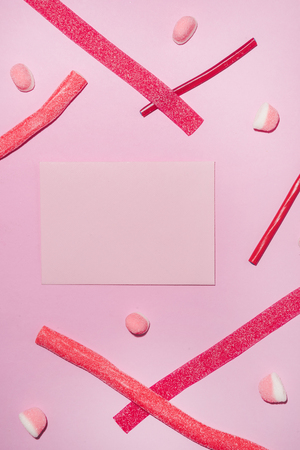 Top view of red sugar candies and lollies with blank sheet of paper isolated on pink background
