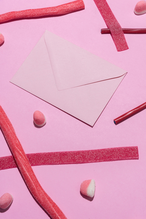 Top view of red sugar candieswith blank envelope isolated on pink background