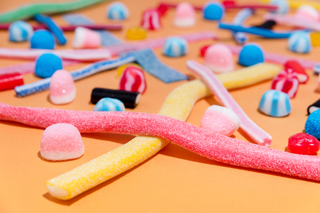 Close up of a mixed colorful candies jellies on the pink background