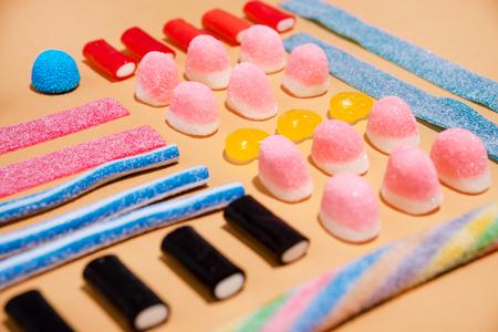 Ciérrese para arriba de las jaleas de un caramelo coloridas mezcladas en el fondo rosado