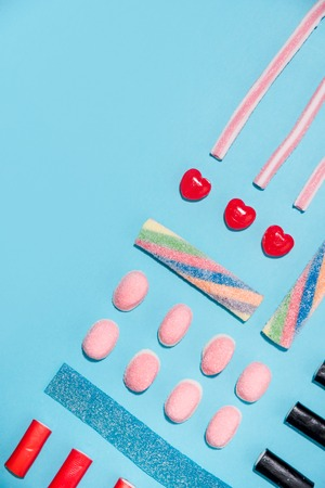 Top view of a group of colorful tasty sweet candies making a pattern over blue background