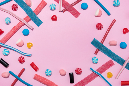 Mixed colorful candies jellies with copyspace in the middle isolated on pink background