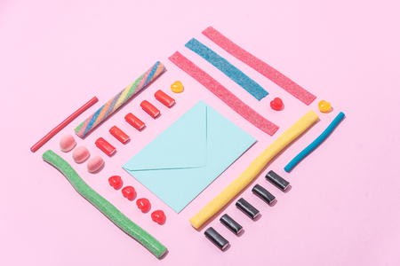 Group of tasty colorful sugar candies and blank paper envelope over pink background