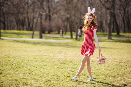 Full length portrait of a young pretty red head woman walking in park with basket and hunting for easter eggs