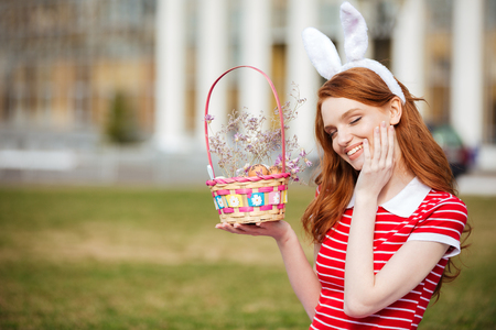 Portrait of a cute smiling red head girl with closed eyes holding easter basket with eggs while sitting in park Stock Photo