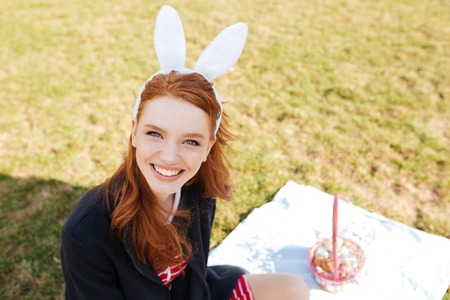 Portrait of a smiling cheerful girl with long red hair wearing bunny ears and having easter picnic outdoors