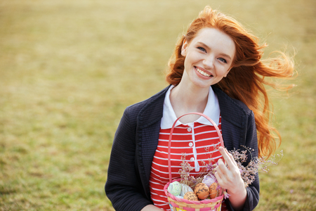 Portrait of a smiling red head girl with long hair holding easter picnic basket with eggs and looking at camera while resting in park Stock Photo