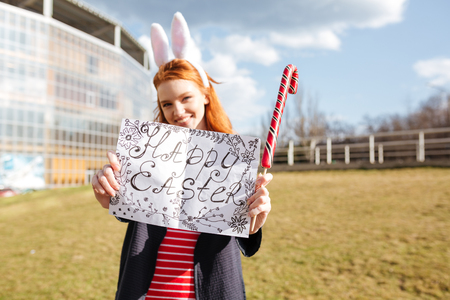 rabbit standing: Portrait of a friendly smiling girl with red hair holding happy easter board and looking at camera outdoors