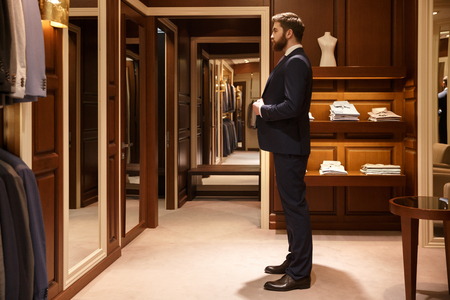 Side view of bearded man which tries on a suit while being in a shop. Full  length portrait