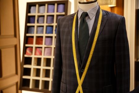 それを巻尺でハンガーに市松模様の男性スーツ ジャケットの写真