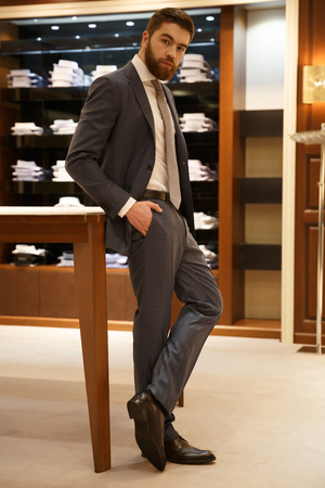 Vertical image of bearded man in suit posing in shop and looking at camera
