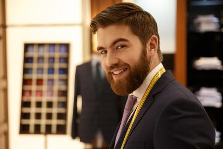 Portrait of cheerful bearded man in blue suit in cloakroom