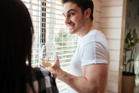 Shot of man with champagne looking at his woman near window