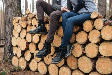 Shot of legs of man and woman sitting on logs in forest