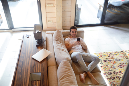 Full-length shot of cheerful man with phone lying on soft couch Stock Photo