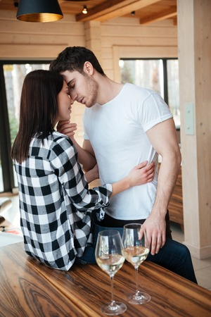intimately: Vertical shot of lovers man and woman kissing on table near glasses with champagne at home