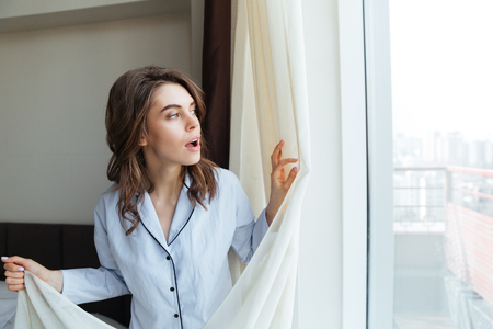 Young lovely woman opens curtains to look at the view out of a window Stock Photo