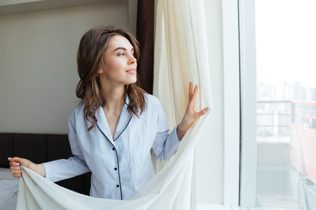 Portrait of a happy woman in nightwear opening window curtains in the morning photo