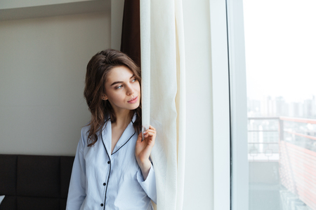 Attractive lovely woman looking at the view out of a window photo