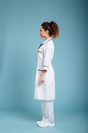 Full lenght side view photo of a concentrated young nurse with stethoscope looking aside isolated over blue background.