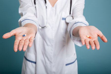 Young woman doctor showing two pills in hands over blue background.