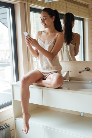 bathroom mirror: Cheerful pretty young woman sitting and using cell phone in bathroom