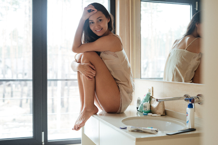 bathroom mirror: Smiling gorgeous young woman sitting in bathroom in the morning Stock Photo