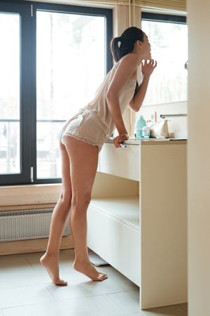 nightwear: Attractive young woman with toothbrush standing and looking at the mirror in bathroom