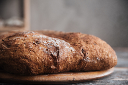 Photo of bread with flour on dark wooden table at bakery
