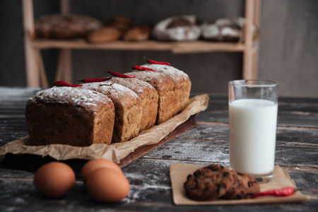 buttery: Image of bread with flour on dark wooden table with milk and cookie near eggs at bakery Stock Photo