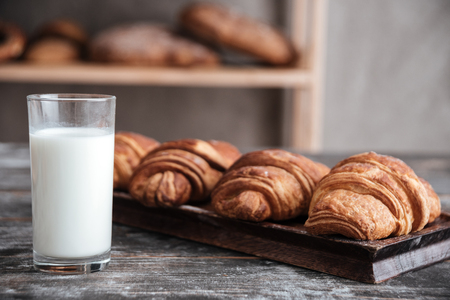 Image of croissants on dark wooden table with milk at bakery