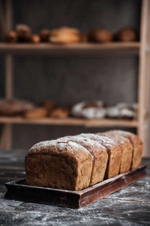 buttery: Image of bread with flour on dark wooden table background at bakery