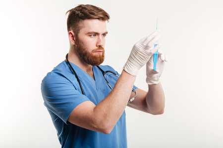Portrait of a serious surgeon holding a syringe isolated on white background
