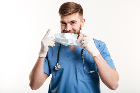 Portait of a young male medical doctor or nurse putting sterile mask isolated on white background