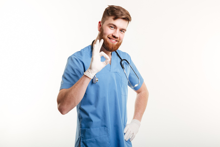 Portrait of a friendly happy male doctor showing ok gesture with two hands isolated on white background Stock Photo