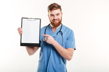 행복 친절 한 젊은 의사 또는 흰색 배경에 고립 된 빈 종이 클립 보드에 손가락을 가리키는 간호사의 초상화