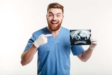 Portrait of a happy excited male medical doctor or nurse pointing finger at radiograph x-ray image isolated on white background