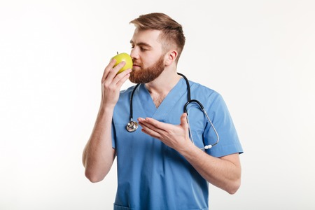 健康医師の肖像画白い背景の上分離されたリンゴの臭いがして指摘 写真素材
